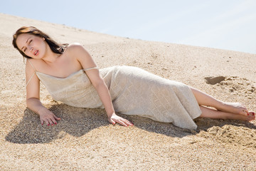 Beautiful brunette  layed down on the sand