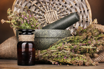 Thyme herb and mortar on wooden table on brown background