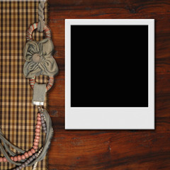 Instant photo frame on wooden background, vintage style