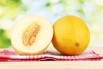 Ripe melons on wooden table on natural background