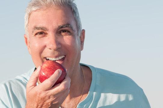 Mature man eating an apple