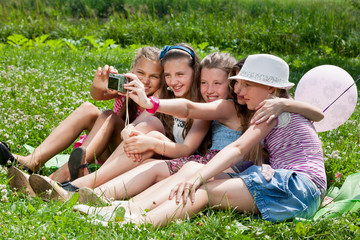 beautiful girls taking picture on grass in city park outdoors