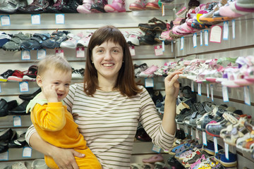 Happy mother with child chooses baby shoes