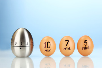 egg timer and eggs on blue background