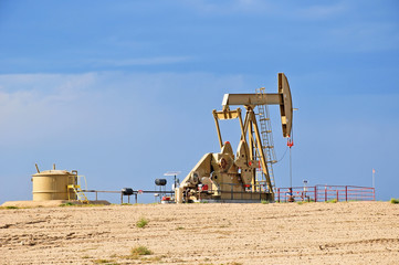 Low view of a working oil pump jack pumping crude.