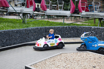 Lovely toddler driving car in amusement park