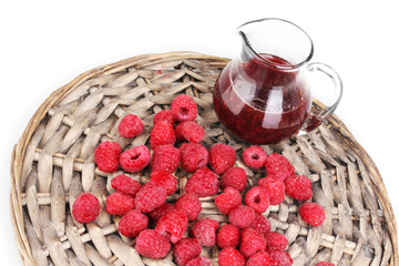 Raspberries and jug with jam on wicker mat isolated on white