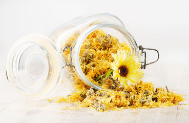 Calendula - medicinal herbs on wooden table
