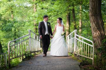 brautpaar läuft hand in hand über eine brücke