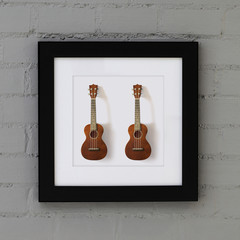 ukulele in frame on the wall