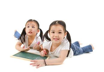 Little Asian girl drawing, lying on floor