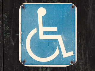 Old wheelchair sign on a wooden wall