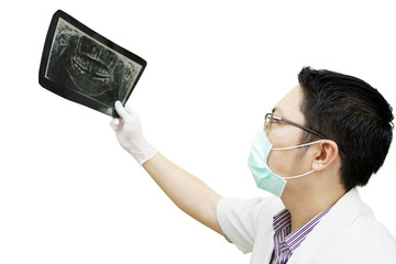 Male dentist checking x-ray