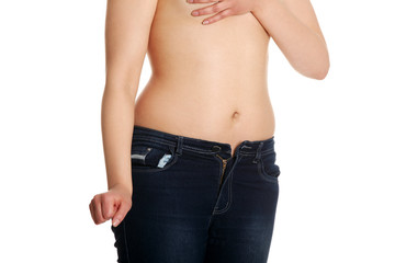 Naked belly of young woman wearing only jeans.