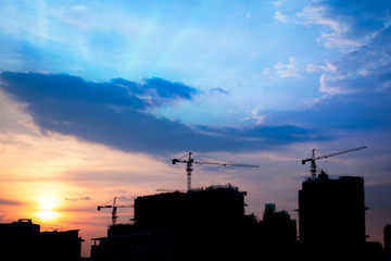 Industrial construction cranes and building silhouettes at sunse