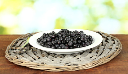 Fresh blueberries in plate on green background