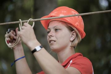 The girl in a helmet hangs on the tense rope