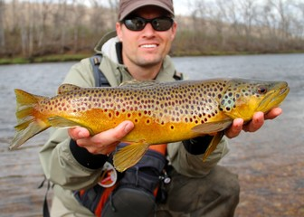 Fly fisherman holding a huge Brown Trout fish