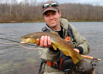 Fly fisherman with Brown Trout, fly rod and reel, in a river