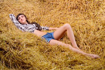 Young woman on haystack