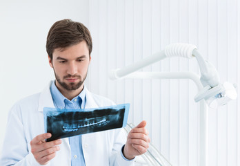 Dentist carefully examines the roentgenogram, whte background.