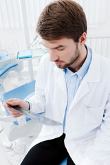 Dentist deeply examines the roentgenogram, whte background