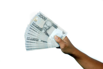 male hand holding a sheet of paper currency Indonesian currency