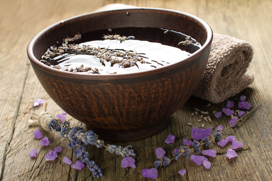 Bowl of water and lavender petals on old wood. Spa treatments