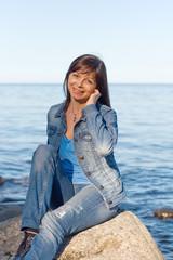 Женщина сидит на камне на берегу озера