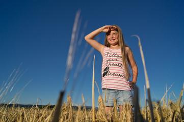 Mädchen im Getreide schaut in die Ferne