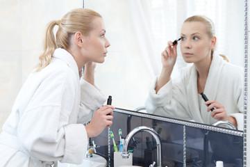 Pretty woman mascaras her eyelashes in bathroom