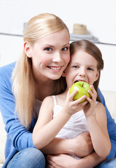 Smiley mum with her eating green apple daughter