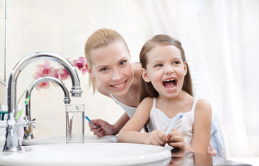 Little girl brushes her teeth with her mother