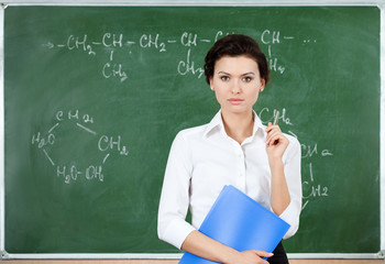 Serious teacher stands at the blackboard