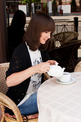 Красивая девушка в летнем кафе пьет чай