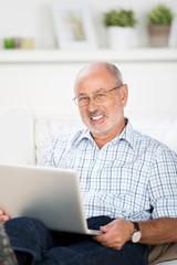 senior sitzt entspannt mit laptop auf dem sofa