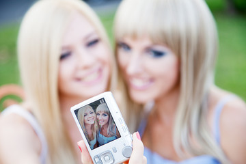 Two beautiful young girl friends with a photo camera