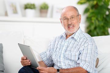 älterer mann sitzt mit tablet-pc auf dem sofa
