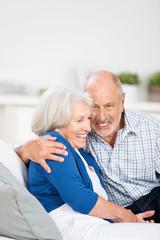 glückliches älteres ehepaar auf dem sofa