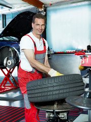 Car mechanic in a garage is fitting a summer tyre