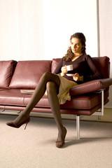 Frau sitzt im Ledersofa