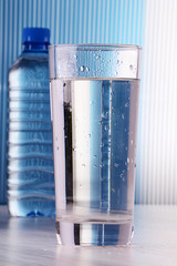 Composition with glass and bottle of water on blue background