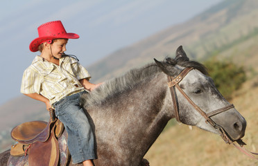 young happy boy in cowboy hat riding horse outdoors