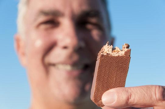 Mature man eating chocolate