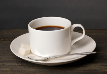 Coffee cup on wooden table on grey background