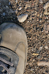 Hiking boot off-road shoe on hard arid dried soil, vertical clos