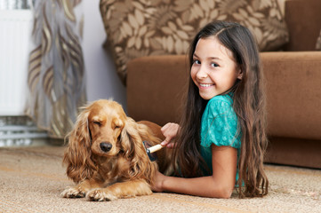 The girl is combing the dog