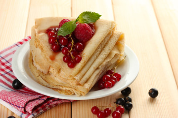 Delicious pancakes with berries and jam on plate on wooden