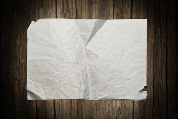 Aged crumpled paper on wood
