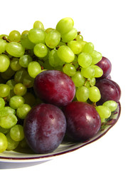 Green grapes and plums on a plate isolated on white background c